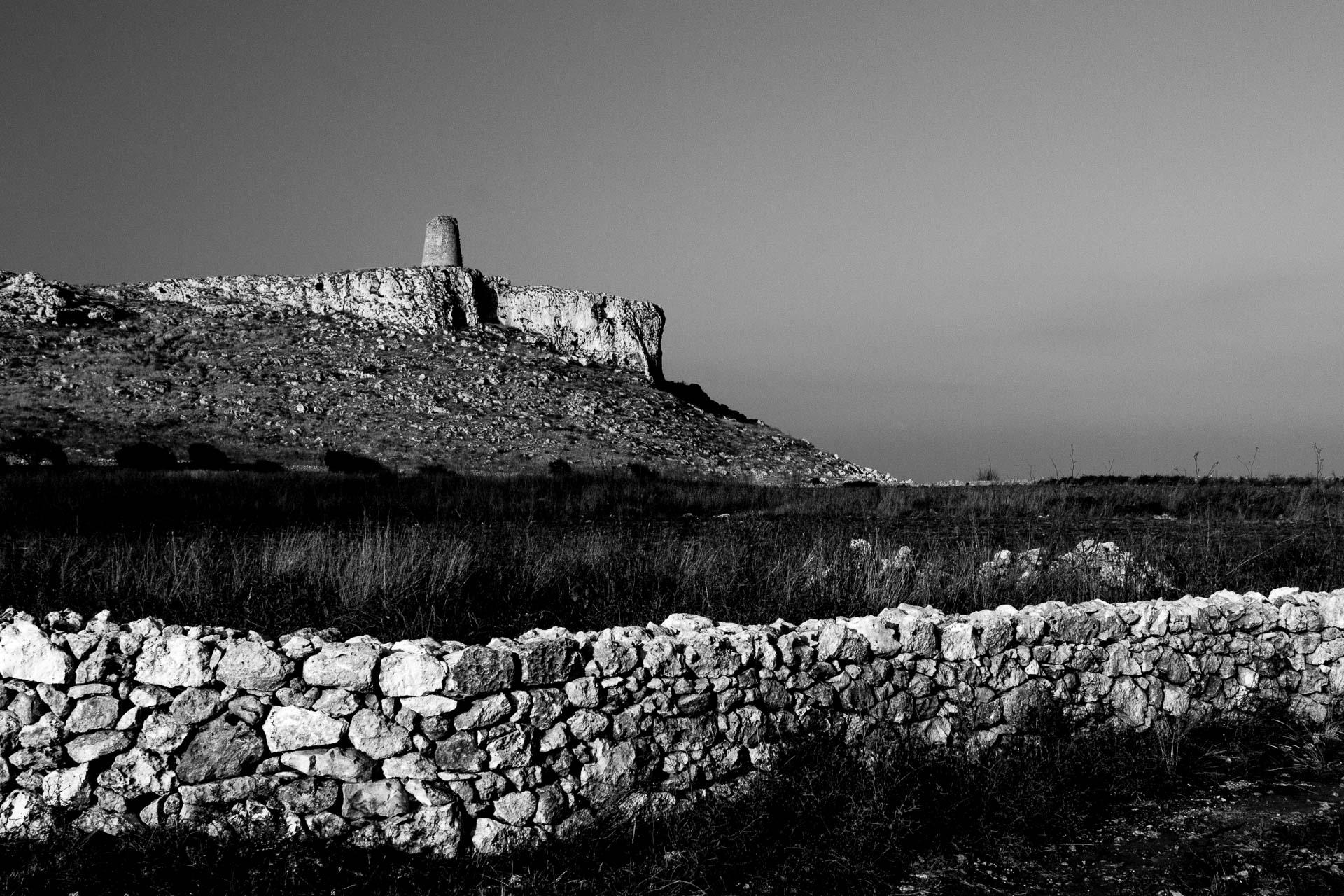 Paesaggio di pietra senza tempo, la torre costiera di avvistamento di Torre Sant'Emiliano, vicino Otranto, con un muretto a secco