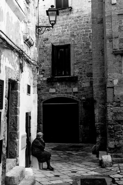 Anziana signora seduta su una pietra vicino casa