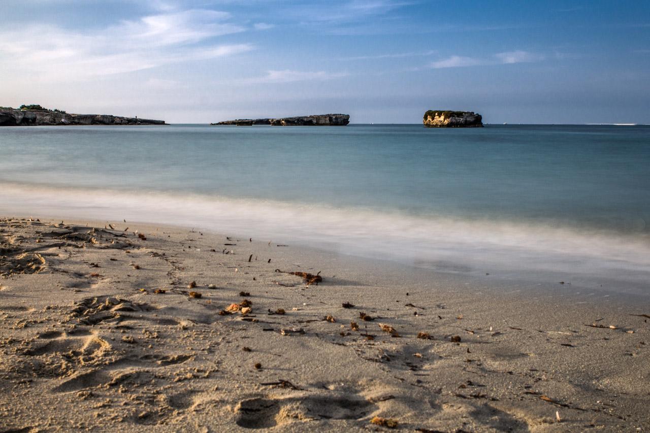Orme sulla sabbia e il mare catturato con una lunga esposizione, Torre Specchia