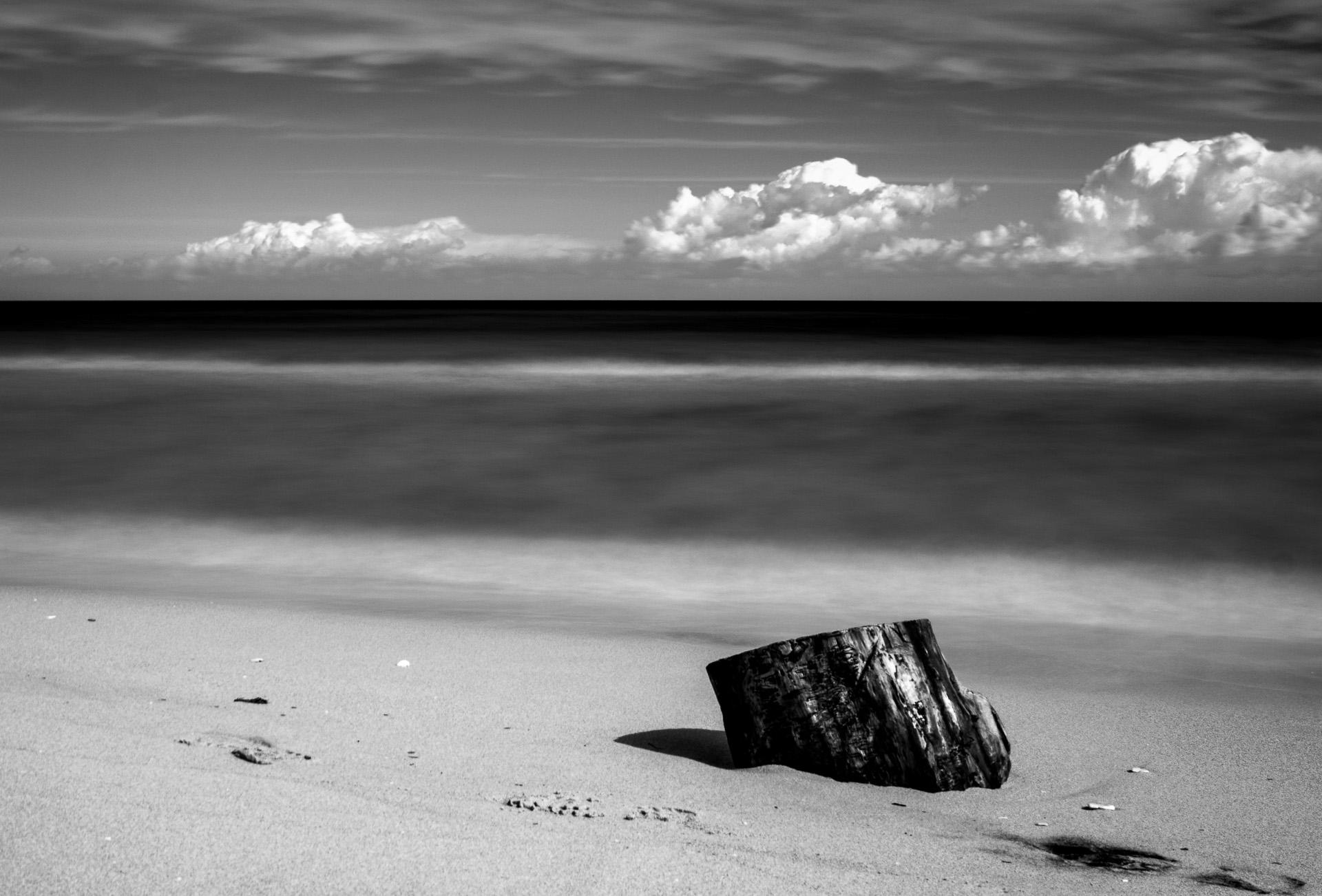 Tronco sulla spiaggio e nuvole, black and white long exposure photography
