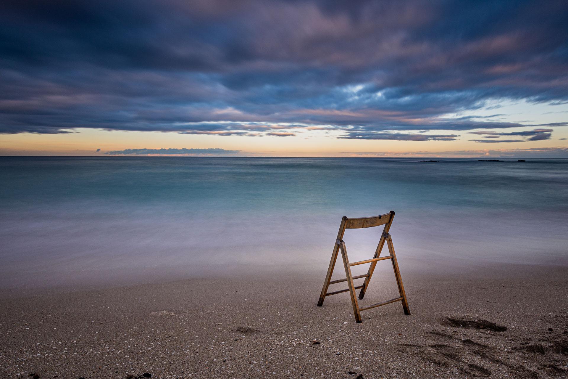 Sedia in riva al mare al tramonto, seascape long exposure photography. Essere senza tempo